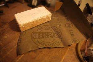 Zu sehen ist ein Schleifblock der auf Schleifpapier liegt. Der Schleifblock ist weiß angemalt. Das Schleifpapier liegt auf einen Holzuntergrund. Daraduf geschrieben ist P 240 und ein großes Symbol. Dieses symbolisiert Hermes, best quality warranted