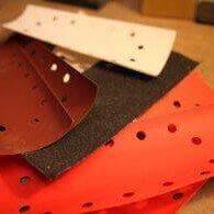 Auf einem Tisch liegt Schleifpapier. Dabei Handelt es sich um Schleifpapier für den Schwingschleifer und für einen Holzklotz. Das Schleifpapier hat Löcher, sodass der Schwingschleifer eine Absaugfunktion besitzt. Die Schleifpapiere haben verschiedene Farben und Körnungen. Die Farben sind rot, braun, schwarz und weiß.