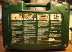 Zu sehen ist die Rückseite eines Koffers, des Elektrowerkzeugs Bosch PEX 300 AE. Darauf befinden sich vier Spalten. Dort befinden sich vier Punkte mit Beschreibung. Diese sind in 32 Sprachen aufgeführt.