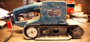 Ein Bandschleifer von der Seite fotografiert. Er ist blau und die Zeichen von AEG sind zu sehen.