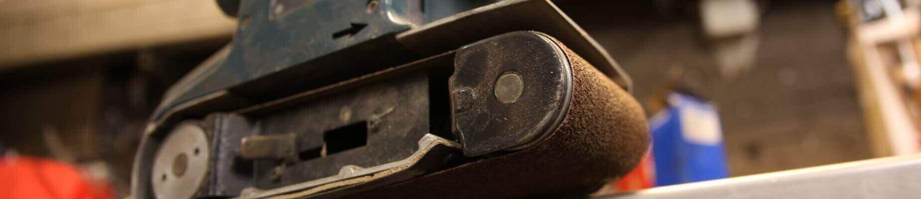 Ein Bandschleifer von ganz nah. Das Foto wird von unten geschossen, sodass man unter das Schleifband sehen kann. Dies kann nur zustande kommen, da die Schleifmaschine auf einem Absatz steht. Der Bandschleifer ist in einem blauen Farbton gehalten und scheint von der Firma AEG zu sein.