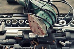 Ein Deltaschleifer in grüner Farbe und dem Kabel um das gerät gewickelt