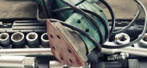 Ein Dreieckschleifer liegt mit seinem oberen Teil auf einem Stecknüsse Set. Das Kabel ist rustikal um den grünen Deltaschleifer gebunden.