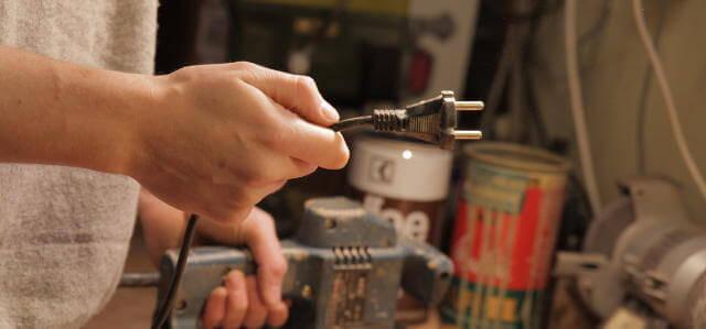 Ein Mann hält in seiner rechten hand einen Stecker. Er hält ihn vor sich. er trägt einen grauen Pullover. Mit seiner linken Hand hält er eine Schleifmaschine fest, die auf einem Tisch zu stehen scheint. Im Hintergrund ist ein wenig Chaos.