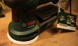 Zu sehen ist das Gehäuse des Exzenterschleifers PEX 300 AE. Es besteht aus Plastik. Das Bosch Logo ist in silber und die Bosch Schrift in rot. Die Schleifplatte in weiß gehalten. Außerdem sieht man die Staubkassette und eine Beschreibung die an dem Griff hängt.