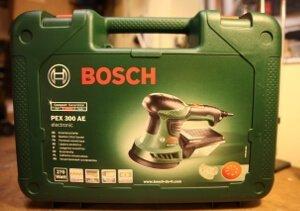 Aufgenommen wurde das Bild auf einer Werkbank. Dort steht der Koffer des Bosch PEX 300 AE Exzenterschleifer.