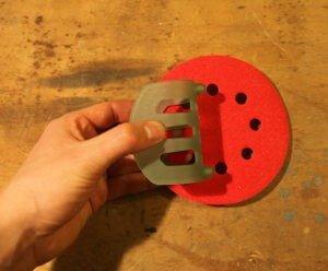 Ein rotes Schleifblatt und ein Paper Assistent. Das Blatt liegt auf einem Tisch. Der Assistent wird durch eine Hand festgehalten. Die Noppen zeigen in Richtung der Löcher des Blattes.