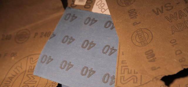 Schleifpapier liegt kreuz und Quer herum. Es sind immer die Rückseiten zu sehen. Dadurch sind die Stärken der Körnungen ersichtlich. 40, 60, 240, 1000 sind zu sehen. Auch der Name Hermes ist erahnbar.