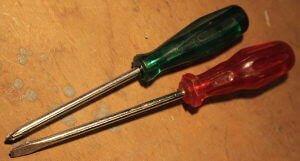 Zwei Schraubenzieher sind zu erkennen. Sie haben einen roten und grünen Griff. Am Ende des Stils befindet sich jedoch ein unterschied zwischen die zwei Schraubenziehern. Es sind ein Kreuzschlitz- und Flachschraubendreher.