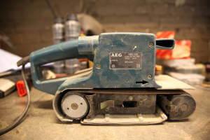 Ein Bandschleifer von AEG in einem hellblauen Design steht auf einem Tisch. Das Gerät wird der Kabel angetrieben.