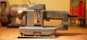 Ein Schwingschleifer von AEG ist zu sehen. Er hat eine blaue Farbe und steht auf einem Tisch. Im Hintergrund befinden sich Dosen und ein weiteres Schleifgerät.