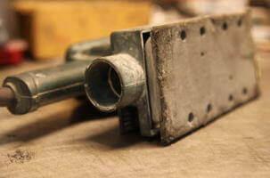 Ein Schwingschleifer liegt auf der Seite. Er sieht sehr benutzt aus und die Schleifplatte müsste erneuert werden.