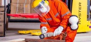 Ein Handwerker schleift ein Stück Metall. Er ist in voller Sicherheitsmontur gekleidet. Er trägt einen orangenen Ganzkörperanzug, Knieschoner, einen Sichtschutz, Ohrschutz und einen Mundschutz. Er schleift mit einem Winkelschleifer. Alle Farben die er trägt sind hell.