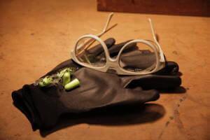 Eine Schutzbrille, Handschuhe und zwei Ohr stopfen liegen beieinander. Sie liegen auf einem Hölzernen Untergrund.