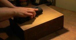 Eine Kiste wird gerade per Hand von einer jungen Männerhand abgeschliffen. Der Arbeitsort ist eher etwas dunkler. Nur die Arbeitsstelle ist sehr hell.