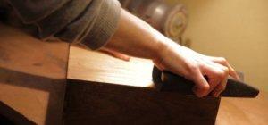 Die Hand eines jungen Mannes greift um einen Schleifblock, der umwickelt ist mit schwarzen, grobem Schleifpapier. Er schleift gerade eine Holzkiste. Dabei wird die Oberfläche abgeschliffen.