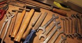 Auf dem Bild sind mehrere Werkzeuge zu erkennen. Von den Pfeilen bis zur Säge ist alles dabei. Alles liegt relativ geordnet auf einem hölzernen Tisch. Es sind viele Farben zu erkennen. Rot, Blau, neon Grün, einige Varianten von Braun und Silber.