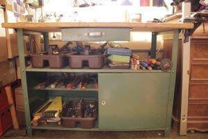 Eine Werkzeugbank ist zu sehen, unter der sich allerlei Werkzeug befindet. Es ist in Arten geordnet. Zur Unterstützung gibt es drei Plastikbehälter. In denen befinden sich immer dir passenen Werkzeuge. Es gibt zusätzlich eine Schublade und einen Bereich der mit einer Tür versehen ist.