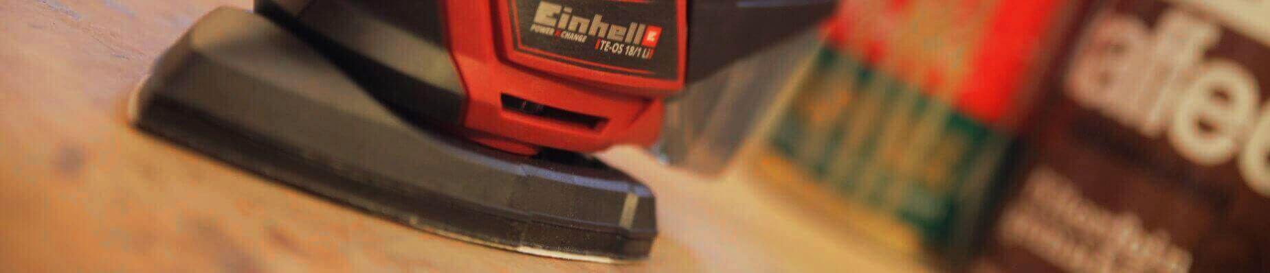Eine Nahaufnahme des Multischleifers Einhell TE-OS 18-1 Li Solo. Das rot, schwarze Gerät ist nicht ganz zu erkennen. Sichtbar ist der Name und die Firma. Außerdem ist die seitliche Struktur der Platte zu erkennen.
