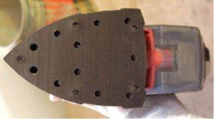 Eine schwarze Klett Schleifplatte mit 11 Löchern für die Funktion der Staubabsaugung.
