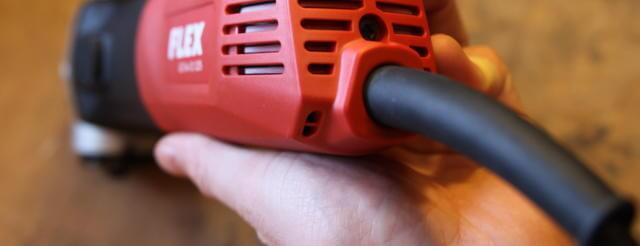 Das rote Gehäuse einer Schleifmaschine von Flex. Das schwarze Kabel steht im Fokus und kommt aus dem hinteren Teil des Winkelschleifers heraus.