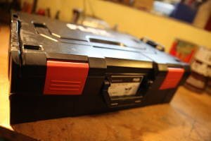 Ein schwarzer Transportkoffer mit roten Schlallen. Der Koffer ist von der Firma Flex.