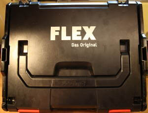 Eine schwarze Oberfläche des Flex Koffers. Die vier Buchstaben stehen in weißer Schrift genau mittig. rechts darunter die Worte 'Das original'.