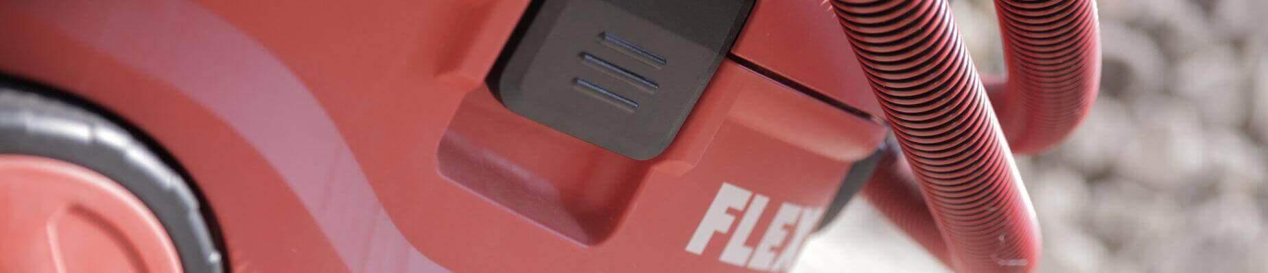Eine Nahaufnahme des Industriestaubsaugers von Flex VCE 33 MAC. Die Farben sind rot weiß und schwarz. Man sieht auf dem Bild teile des Schlachs, ein wenig vom Rad und teilweise das Gehäuse des Saugers.