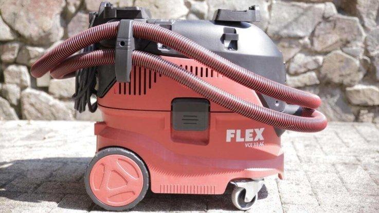 Von der Seite ist der Industriestaubsauger VCE 33 MAC von der Firma Flex zu sehen. Er ist in den Farben Rot, Schwarz und Weiß gehalten. Er steht vor eine Natur Steinwand und auf einem gepflasterten Boden. Das Hinterrad ist um einiges größer als das Vorderrad. Der Schlauch ist mehrfach um den Industriestaubsauger gewickelt.