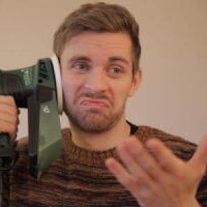 Ein junger Mann hält deinen Exzenterschleifer an sein Ohr und simuliert ein Gespräch. Seine linke Hand ist gehoben und ist im Vordergrund sichtbar.