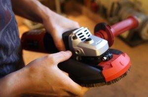 Das Kombinationsgerät von Flex, der Betonschleifer, Fließen Schneider und Winkelschleifer. Eine männliche Person hält die Schleifmaschine in beiden Hände und macht eine Untersuchung.